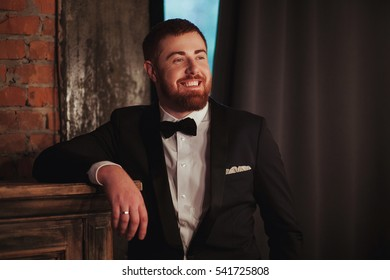 portrait of young handsome smiling ginger man with beard in the dark room