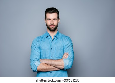 A portrait of young handsome smiling man in jeans shirt standing with crossed hands.