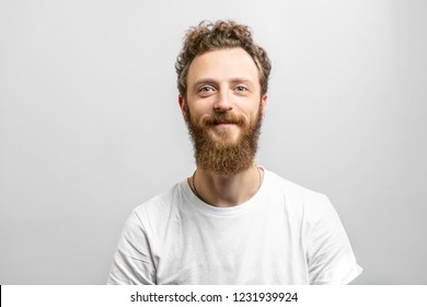 Portrait of young handsome softie, good-looking kind hipster man with beard smiling and looking at camera over white background.
