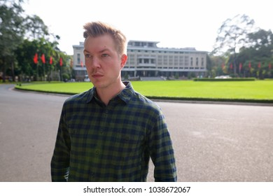 Portrait of young handsome tourist man exploring Ho Chi Minh city in Vietnam