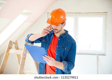 Portrait of young handyman holding clipboard in his hand and making call while standing at construction area.