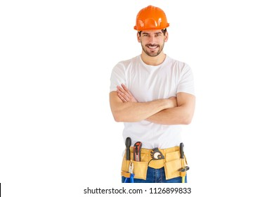 Portrait of young handyman wearing hard hat and tool belt while standing with arms crossed at isolated white background with copy space.