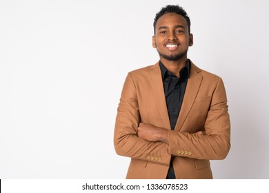 Portrait of young happy African businessman smiling with arms crossed