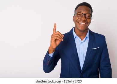 Portrait of young happy African businessman pointing up