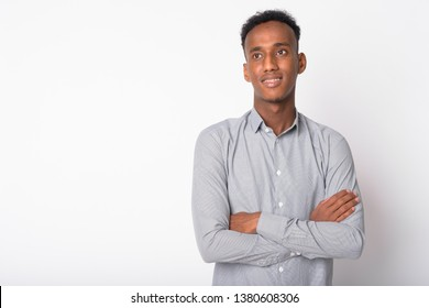Portrait of young happy African businessman thinking with arms crossed
