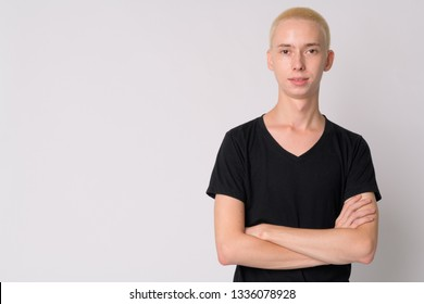 Portrait of young happy androgynous man smiling with arms crossed