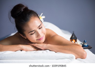 portrait of young happy Asian beautiful woman relax in spa. Body care treatment. Cute girl having massage at back by professional massager hands with candle and white Plumeria on bed.