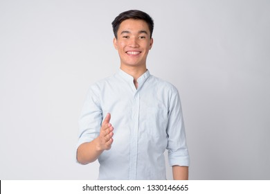 Portrait of young happy Asian businessman giving handshake