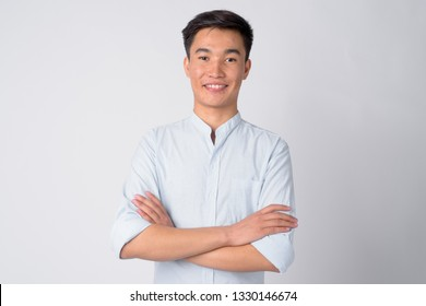 Portrait of young happy Asian businessman smiling with arms crossed