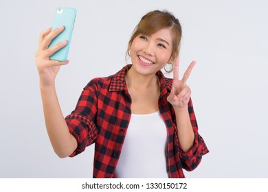 Portrait of young happy Asian hipster woman taking selfie with peace sign