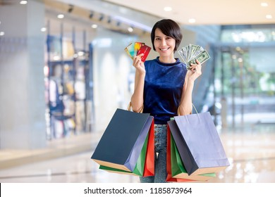 Portrait of young happy Asian woman with her colorful shopping bags showing her credit cards and a bunch of dollar bills in the shopping mall