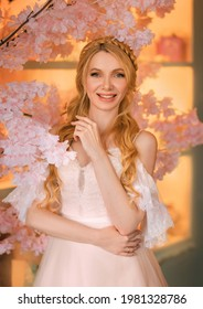 Portrait of young happy beautiful blonde woman in white vintage dress. Girl laughs, smile on face. Studio background, blooming pink sakura tree. Long hair is braided into an elegant romantic hairstyle - Shutterstock ID 1981328786