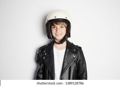 Portrait of Young happy beautiful teen kid in black leather jacket and white moto helmet smiling on white background