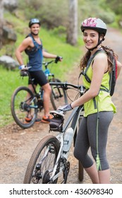 Portrait of young happy biker with man on footpath in forest