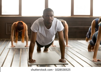 Portrait of young happy black man and a group of sporty people practicing yoga lesson standing in Plank pose, doing Push ups or press ups exercise, working out, indoor full length, studio