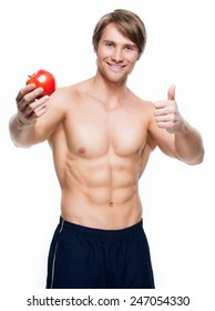 Portrait of young happy bodybuilder holding apple in his hand and show thumbs up sign - isolated on white background.