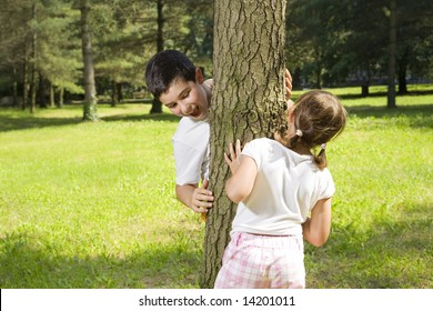 Portrait of young happy boy and girl playing hide and seek at park.