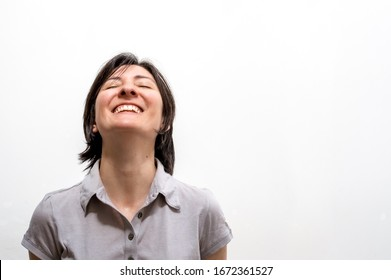 Portrait of a young happy brunette woman standing on a white wall, smiling with closed eyes in a peaceful manner. Happiness and mental health concept.