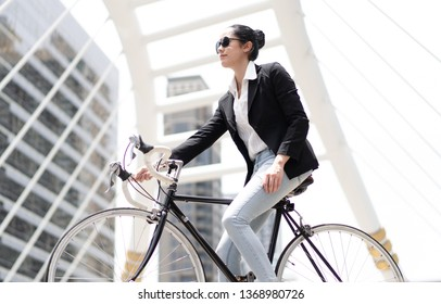 Portrait of Young happy business woman standing and looking away on her bike at city building.Lifestyle Concept