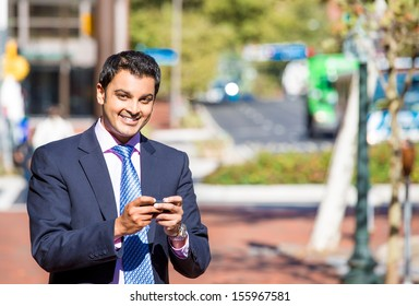 A portrait of a young happy businessman checking  his phone while on a break, isolated on a background of a city street, on a sunny autumn day. Corporate life and  success.  Business communication.