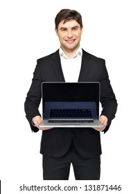 Portrait of young happy businessman holds the  laptop with blank black screen isolated on white.
