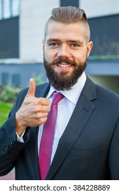Portrait of a young happy businessman. Thumb up. Positive emotions
