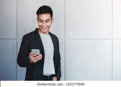 Portrait of Young Happy Businessman Using Smartphone. Standing by the Industrial Concrete Wall. Reading Message via Mobile Phone and Smiling