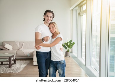Portrait of young happy casual couple, holding a key, bought new apartment for family, newlyweds ready for fresh start, renting flat, housing market, low mortgage rate, cohabiting union, lottery win