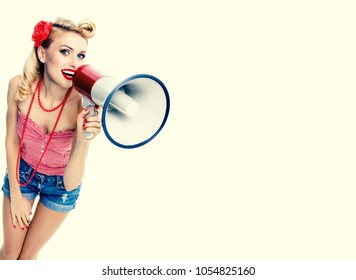 Portrait of young happy caucasian blond woman holding megaphone, dressed in pin-up style, blue jeans shorts with empty copyspace area for text, slogan or advertising message, over yellow background.