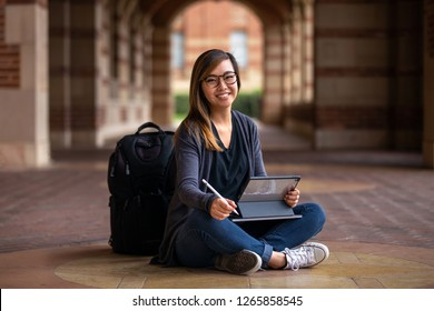 Portrait of a young happy college student sitting with a smart touch pad tablet