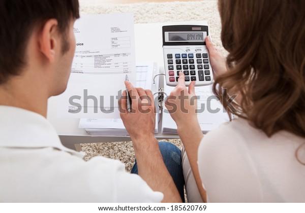 予算を計算する若い幸せな夫婦のポートレート