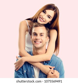 Portrait of young happy couple, close to each other and looking at camera with smile, over pink background. Caucasian models in love, relationship, dating, flirting, lovers, romantic concept.