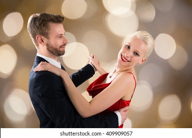Portrait Of Young Happy Couple Dancing On Bokeh Background