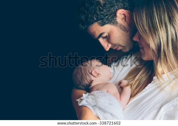 Ritratto di giovane coppia felice che abbraccia e guarda al loro neonato su uno sfondo scuro. Concetto di cura della famiglia e del bambino.