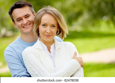 Portrait of young happy couple looking at camera outdoors