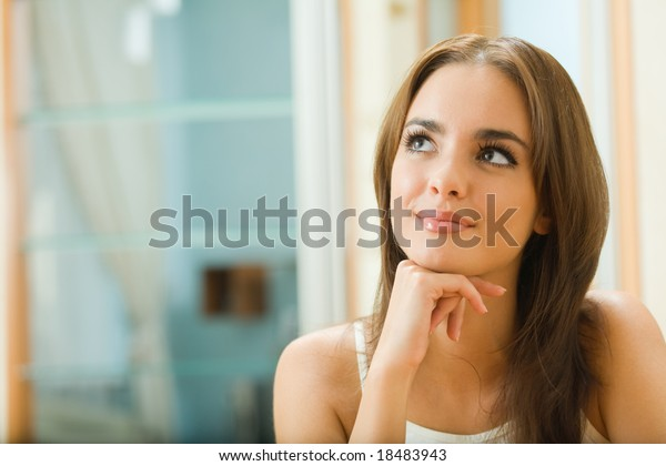 Portrait of young happy dreaming woman at home