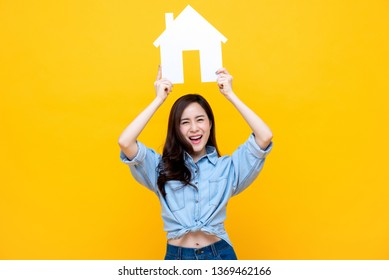 Portrait of young happy ecstatic Asian woman holding paper home for real estate concept