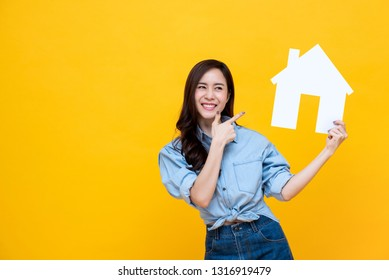 Portrait of young happy excited Asian woman holding paper home for real estate concept