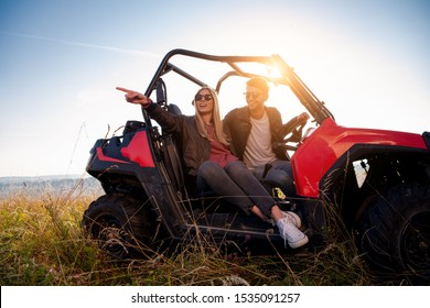 portrait of young happy excited couple enjoying beautiful sunny day while driving a off road buggy car on mountain nature