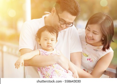 Portrait of young happy family enjoying holiday vacation together, outdoor walking on beautiful sunset.