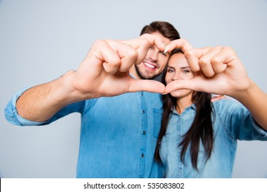 Portrait of young happy family making heart with fingers