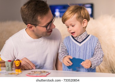 Portrait of young happy father with little cute son making pazzles at home