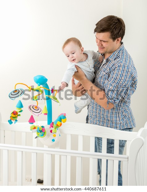 Portrait of young happy father showing new toy carousel in cot to his baby son