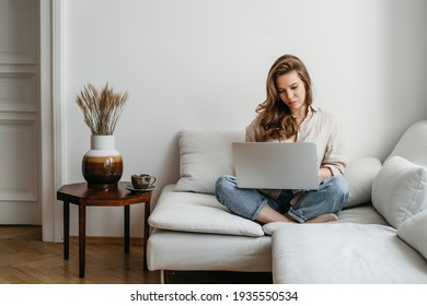 Portrait of a young happy female freelancer sitting on the couch and working on project, watching movie on laptop, studying, blogging, resting and chatting online. High quality photo