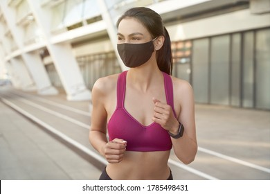Portrait of a young happy fitness woman in short clothes wearing black protective face mask running outdoors in the city during coronavirus outbreak. Covid 19 and physical activity, sport and fitness