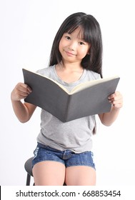 Portrait of young happy girl with book isolated on white (asian, book, child)