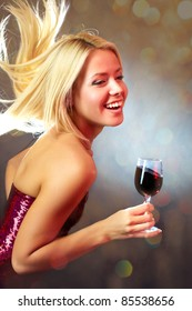 Portrait of young happy girl dancing with wine glass