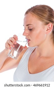 Portrait of a young happy girl drinking water from glass after fitness, isolated on a white background