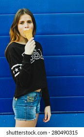 Portrait of young happy girl eating ice-cream, outdoor, over blue wall background