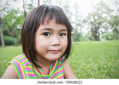 Portrait of young happy girl in the park with green grass background